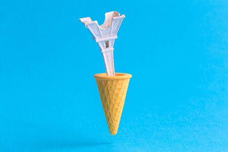 Foto de Ice cream cone with eiffel tower against pastel blue background minimal summertime sweet food and travel creative concept. - Imagen libre de derechos