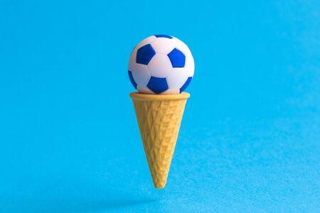 Foto de Ice cream cone with soccer ball against pastel blue background minimal summertime sweet food and sport creative concept. - Imagen libre de derechos