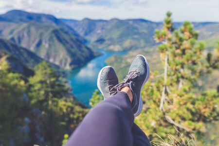 Photo for Woman hiker legs with sports shoes against beautiful valley and hills in the background. Healthy lifestyle and nature concepts. - Royalty Free Image