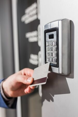 Photo for Man scanning security key card on electric lock to entry private building. - Royalty Free Image