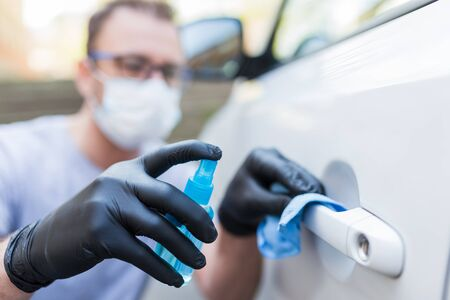 Photo pour Driver with face mask wearing rubber protective gloves wiping and spraying car door handle. Virus and bacteria prevention concept. - image libre de droit