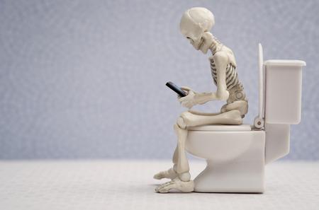 Foto de Skeleton sitting on water closet a smartphone in his hand - Imagen libre de derechos