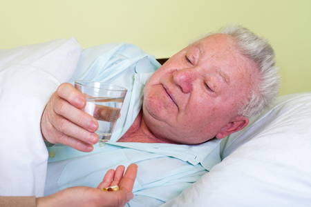 Picture of a sick old man in bed, his caregiver giving him medicine