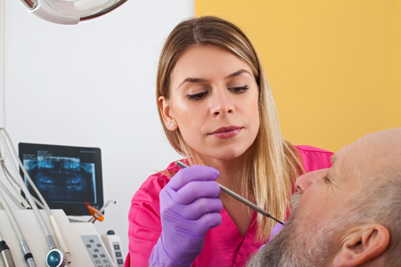 Young female dentist examining mature male patient with periodontal probe