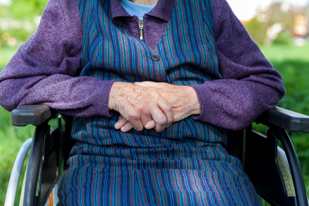 Close up picture of elderly woman's hands, sitting in a wheelchair outdoor
