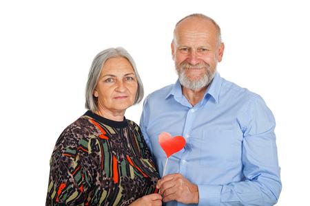 Foto de Senior couple holding red heart photo accessory, smiling to the camera on isolated background - romantic concept - Imagen libre de derechos