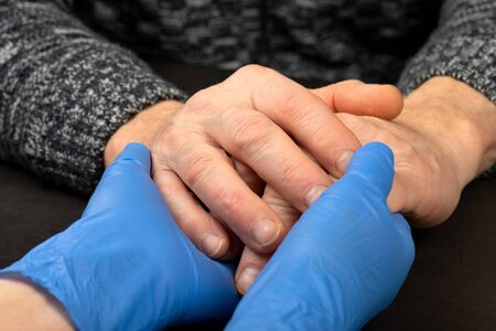 Photo for Caregiver holding elderly patients hand at home - Royalty Free Image
