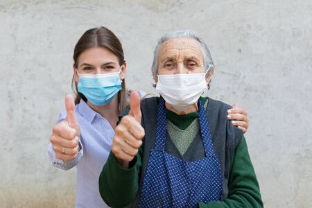 Photo for Portrait of friendly caregiver posing with elderly ill woman wearing surgical mask because of covid-19 pandemic, showing thumbs up - Royalty Free Image