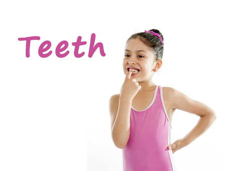 Photo pour  girl wearing a pink swimsuit pointing at her mouth and teeth on a white background for a school anatomy or body part chart - image libre de droit