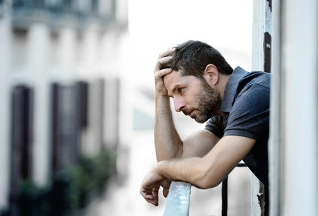 Lonely young man outside at house balcony looking depressed, destroyed, sad and suffering emotional crisis and grief on an urban background