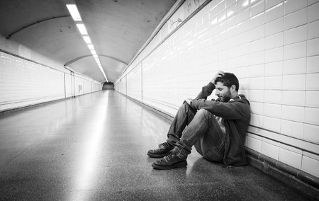 Young man abandoned lost in depression sitting on ground street subway tunnel suffering emotional pain, sadness and looking destroyed and desperate leaning on wall alone