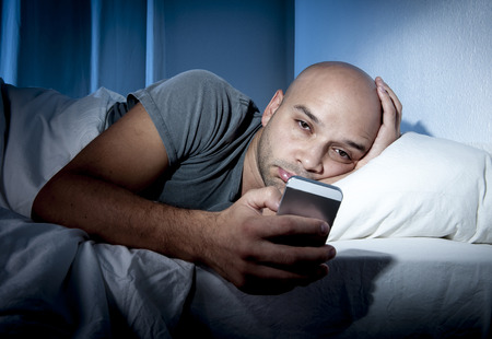young cell phone addict man awake late at night in bed using smartphone for chatting