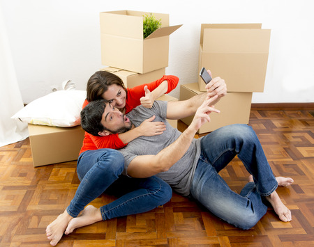 Photo pour young happy couple moving together in a new house , flat or apartment unpacking cardboard boxes home belongings having fun taking selfie video and picture - image libre de droit