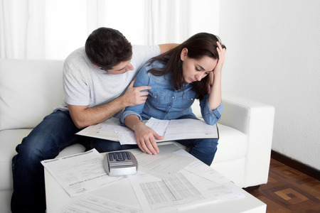 young couple worried home in stress husband comforting wife accounting debt bills bank papers expenses and payments feeling desperate in bad financial situation