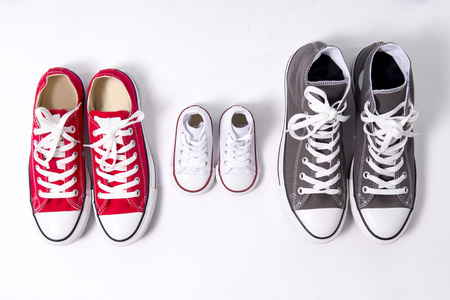 Foto de three pair of shoes in father big, mother medium and son or daughter small kid size representing family, growth, education and togetherness concept - Imagen libre de derechos