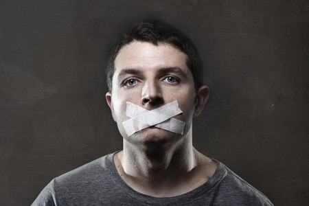 Photo pour attractive young man with mouth sealed on duct tape to prevent him from speaking keeping him mute and censored in freedom of speech and expression concept - image libre de droit