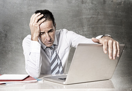 desperate tired senior businessman in crisis working on computer laptop at office desk in stress under pressure facing work problems on grunge studio edition