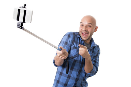 young Hispanic man in casual shirt having fun shooting mobile phone selfie picture or recording video holding stick playing with face expression isolated on white background