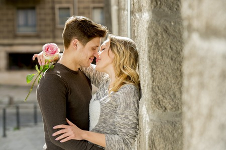 Photo pour candid portrait of beautiful European couple with rose in love kissing on street alley celebrating Valentines day with passion against stone wall on urban background - image libre de droit