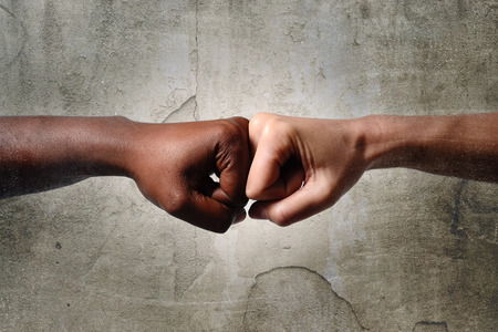 Photo pour black African American race female hand touching knuckles with white Caucasian woman in agreement partnership and cooperation multiracial diversity immigration concept - image libre de droit