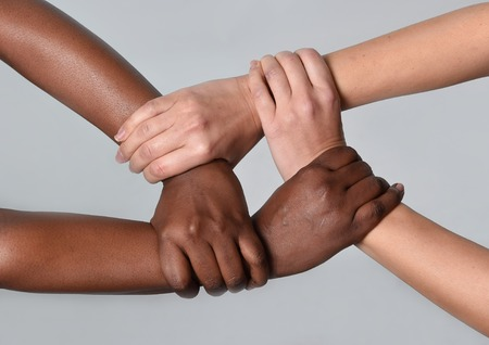 Foto de white Caucasian female hands and black African American holding together in world unity and racial love and understanding in tolerance and races diversity cooperation concept - Imagen libre de derechos