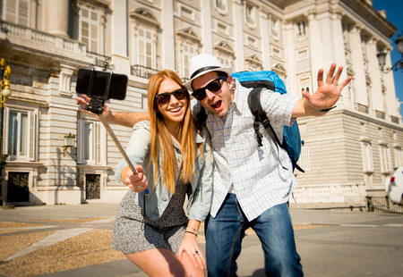 young beautiful friends tourist couple visiting Spain in holidays exchange students and taking selfie stick picture together in town happy on sunny day in travel and vacation concept