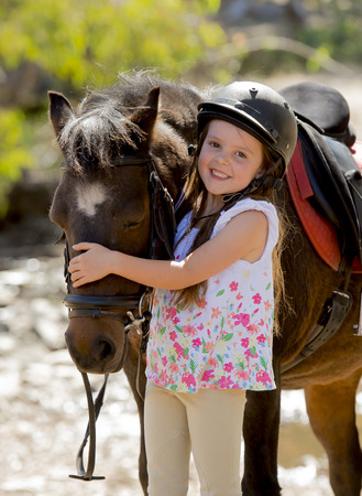 Photo for sweet beautiful young girl 7 or 8 years old hugging head of little pony horse smiling happy wearing safety jockey helmet posing outdoors on countryside in summer holiday - Royalty Free Image