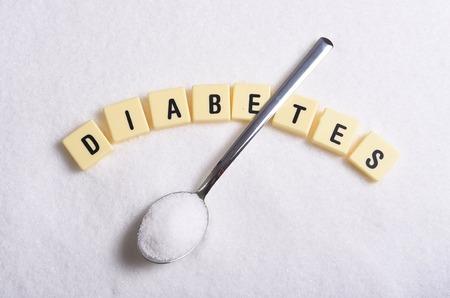 diabetes block letters in crossword and spoon over sugar pile isolated on grainy white sugar texture in sweet food abuse and healh risk of sweet nutrition abuse