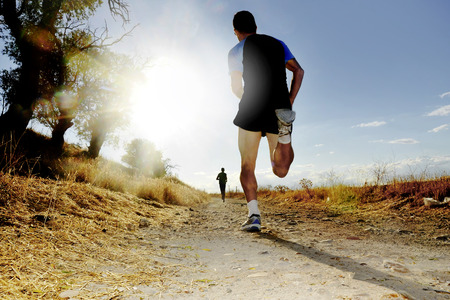 Photo pour Silhouette of young sport man running on countryside in cross country competition at summer sunset with harsh high contrast sunlight effect and flare in healthy lifestyle concept - image libre de droit