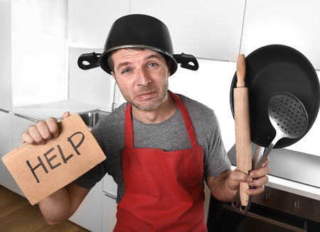 Photo pour funny 30s Caucasian man holding pan and household with pot on his head in red apron at home kitchen asking for help unable to cook showing panic on cooking with funny face expression - image libre de droit