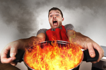Photo for young inexperienced home cook with apron holding pot burning in flames with stress and panic face expression in fire in the kitchen and cooking wrong concept - Royalty Free Image