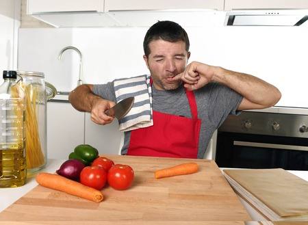 young attractive home cook man in red apron slicing carrot with kitchen knife  suffering domestic accident cutting and hurting his finger while cooking in pain face expression