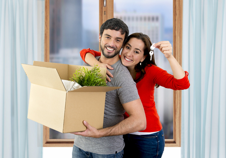 Photo pour young happy Hispanic couple moving together in a new flat or apartment carrying cardboard boxes home belongings holding house key smiling in housing and real state concept - image libre de droit