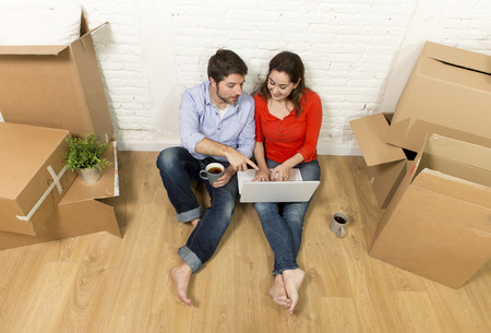 Photo pour young happy American couple sitting on floor moving in a new house or apartment flat using computer laptop choosing online furniture and household in real estate and independent lifestyle concept - image libre de droit