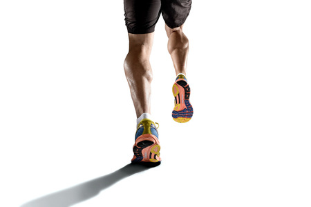 Foto de close up view strong athletic legs with ripped calf muscle of young sport man running isolated on white background with copy space in sport fitness endurance and high performance concept - Imagen libre de derechos