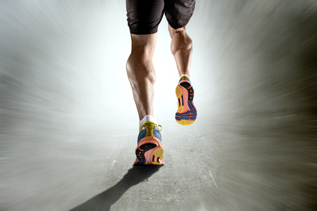 Photo for close up view strong athletic legs with ripped calf muscle of young sport man running isolated on motion grunge background in sport fitness endurance and high performance concept - Royalty Free Image