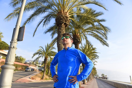 young runner man posing at beach palm trees boulevard with sunglasses in morning jog training session in fitness sport and healthy lifestyle concept
