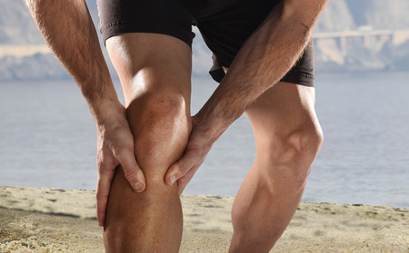Foto de young sport man with strong athletic legs holding knee with his hands in pain after suffering muscle injury during a running workout beach training in muscular or ligament wound - Imagen libre de derechos