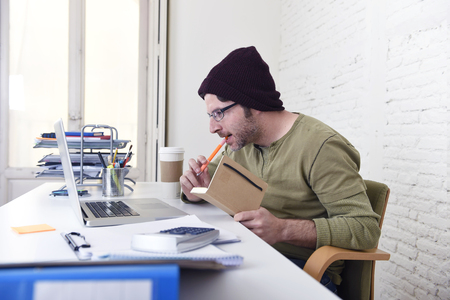 young attractive hipster businessman with take away coffee working from his home office as freelancer wearing beanie looking busy in self employed business model success