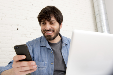 corporate portrait young Hispanic attractive hipster businessman on his 30s working at modern home office with computer laptop using mobile phone wearing casual denim shirt and beard