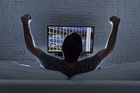 Photo pour back view of young man home alone watching soccer or football game in television enjoying and celebrating goal and victory gesturing with fist sitting on the sofa happy and excited - image libre de droit