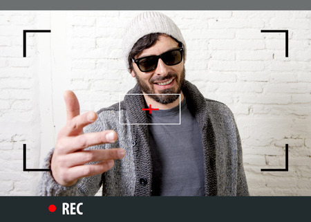 Photo for young attractive vlog hipster and trendy style looking man smiling happy  talking to camera posing cool with attitude dressing informal in selfie and internet video blogger recording - Royalty Free Image
