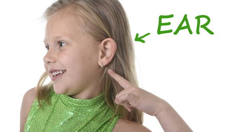 Photo pour 6 or 7 years old little girl with blond hair and blue eyes smiling happy posing isolated on white background pointing ear in learning English language school education body parts card set - image libre de droit