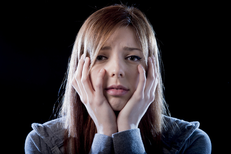 young beautiful teenager girl with red hair feeling lonely and scared looking sad and desperate suffering depression as victim of cyber bullying or social abuse violence and rejection