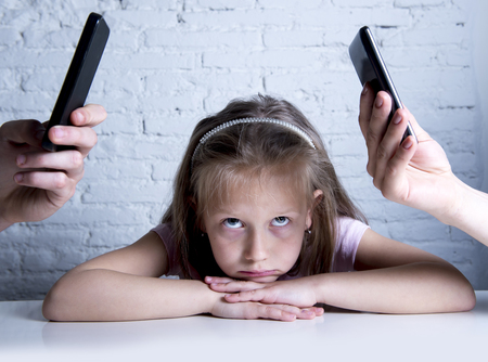 Photo for hands of internet and network addict mother and father using mobile phone neglecting little sad ignored daughter bored and lonely feeling abandoned and disappointed in parents bad behaviour concept - Royalty Free Image