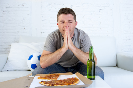 young man alone in stress watching football game on television sitting at home living room sofa couch with ball , pizza box and beer bottle enjoying the match praying nervous and excited