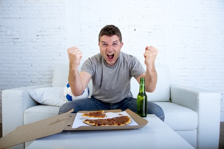 Photo pour young man watching football game on television celebrating goal crazy happy jumping on sofa couch at home with ball beer bottle and pizza looking excited and cheerfull - image libre de droit