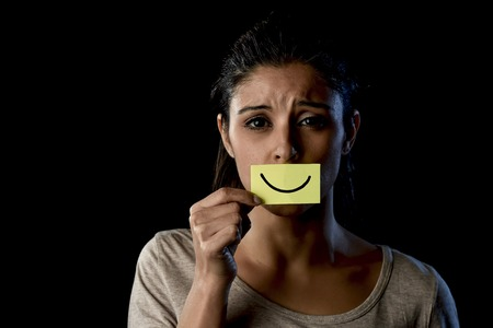 young beautiful Latin sad and depressed latin girl holding paper hiding her mouth behind a fake drawn smile pretending to be happy in depression concept isolated on black background