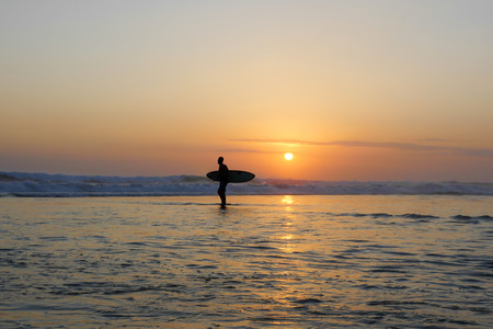 Silhouette of unknown anonymous surfer man holding surf board after surfing on sunset with amazing beautiful sunlight with orange sky and silver sea water in Summer sport and holiday vacation concept