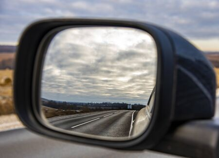 Photo pour The road and the cloudy sky are reflected in the mirror of the car. - image libre de droit